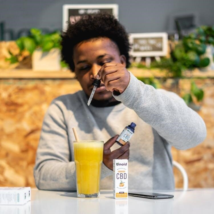 A young man uses CBD oil in his drink